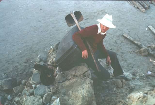 Elder Bernhardt sitting on a rock next to a dead chicken after the Comalapa work day