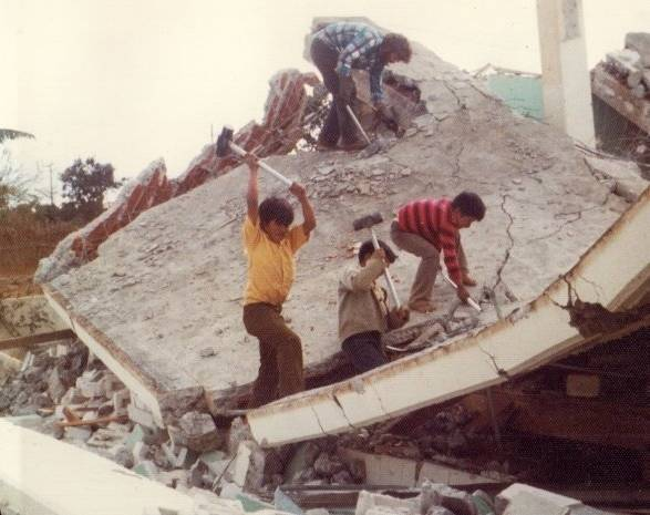 Members help break up the roof at the Patzicía church