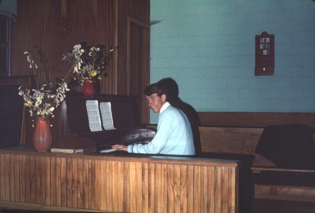 Elder Richman playing the piano at the Patzicía church