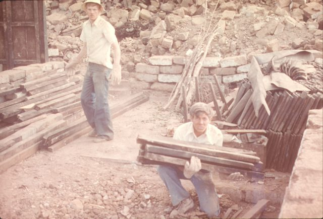 Elders Bernhardt and Richman stacking wood after dismantling a roof in Sumpango