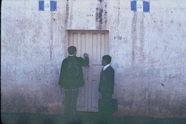 Elder Richman and Elder Choc knocking on a door in Comalapa. (High resolution photo.)